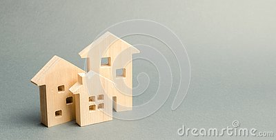 stock image of miniature wooden houses on a gray background. real estate. long-term rental apartments. affordable housing for young families.