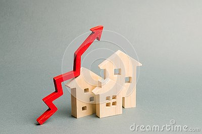 Miniature wooden houses and red arrow up. The concept of increasing the cost of housing. High demand for real estate. The growth