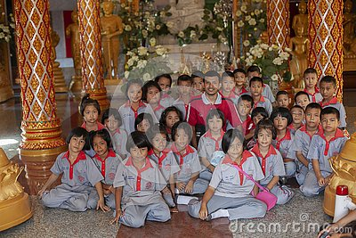 stock image of thailand, phuket, 01.18.2013. elementary school students and a teacher in the buddha temple, group photo. education. training.