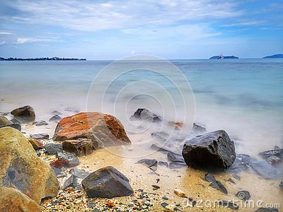 The beautiful silky smooth water waves and rocks on the sea shore.