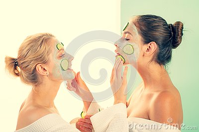 Girls friends sisters in bathrobes making clay facial mask. Anti age care. Stay beautiful. Skin care for all ages. Women