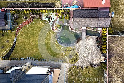 Aerial view of beautifully landscaped recreation house cottage complex with pond in ecological area on bright sunny day. Modern