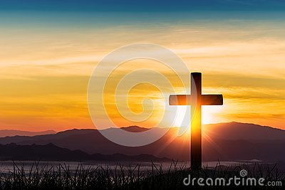 Silhouette of cross on mountain sunrise background