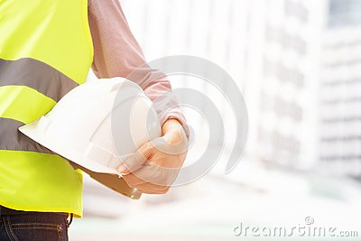 Close up front view of engineering male construction worker holding safety white helmet