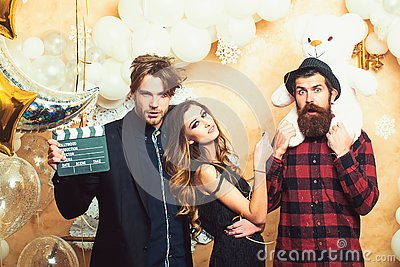 Sensual woman and men in movie or film studio. Boyfriends with movie clapper and teddy bear toy. Cinema theme party for