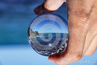 Crystal ball with recletion of Aphrodite bath beach at morning light. Glass/Lens ball holding in hand with blue, clear sea. Sky is