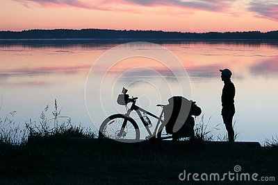 stock image of silhouette of a tourist and a bicycle