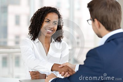 Smiling african hr manager handshake hire candidate at job interview