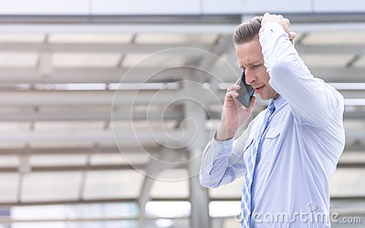 Serious Business man using mobile phone outdoor
