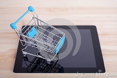stock image of shopping cart over a tablet pc on wooden table
