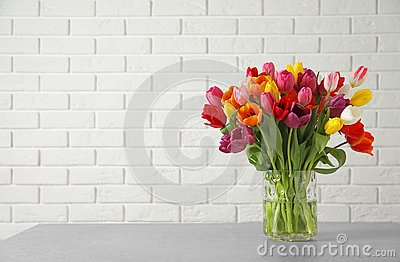 Vase with beautiful spring tulip flowers on table near brick wall.