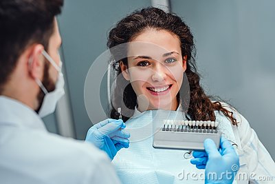 Choice of tooth color with a special scale. Dentist select a shade of tooth enamel for the young pretty girl of the patient.