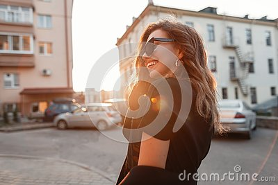 Young happy hipster woman with a positive smile in sunglasses in a stylish T-shirt in a coat in the city near houses