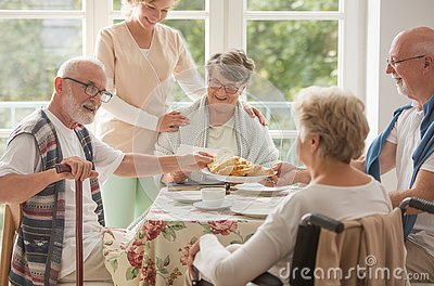 Group of friends with helpful carer sitting together at the table at nursing home dining room and eating cake