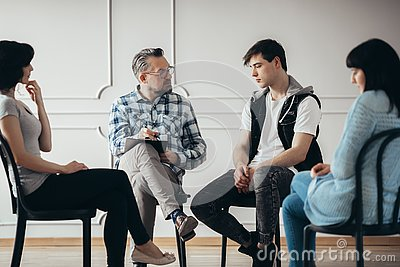 Group therapy with psychologist and depressed man and woman