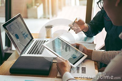 Business partnership coworkers using a tablet to chart company financial statements report and profits work progress and planning