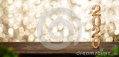 Happy New Year 2020 wood with sparkling star on brown wood table with gold bokeh background,Holiday festive celebration concept.