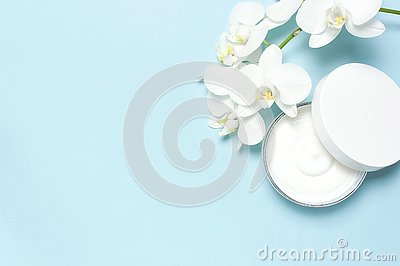 Beauty Spa concept. Opened plastic container with cream and White Phalaenopsis orchid flowers on blue background Flat