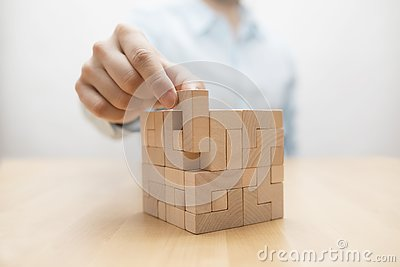 Man`s hand adding the last missing wooden block into place.