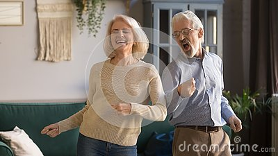 Excited mature couple, man and woman having fun, dancing together