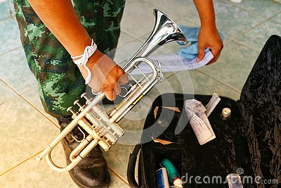 The military hand is holding the instrument.  Silver trumpet dryer type with black box on the floor