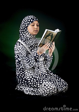 stock image of young beautiful muslim girl reading the holy book of quran