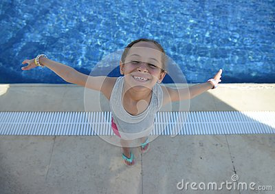 stock image of happy little young girl by swimming pool with open arms