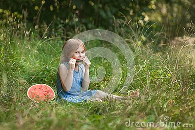 Cute girl eating watermelon in the summer outdoor. Healthy snack for children