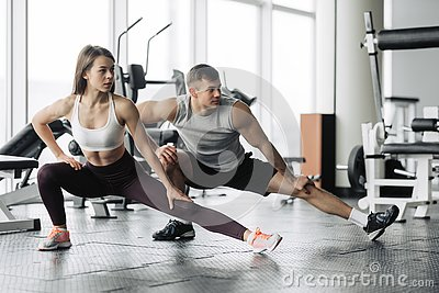 Sport, fitness, lifestyle and people concept - smiling man and woman stretching in gym