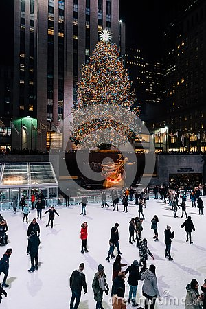 Christmas tree and ice skating rink at Rockefeller Center at night, in Midtown Manhattan, New York City