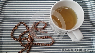 Top view of green tea in a cup with prayer beads or rosary placed in a tray