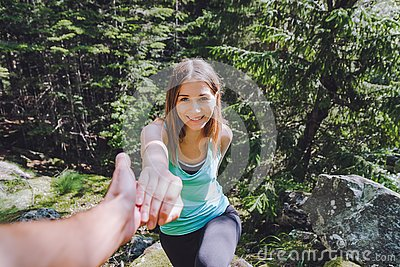 stock image of girl climbs on rock, partner pulls out hand for assistance