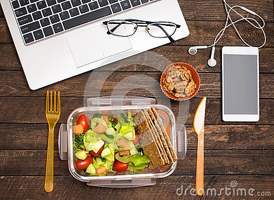 Healthy business lunch at workplace. Salad, salmon, avocado and nuts lunch box on working desk with laptop, smartphone, glasses