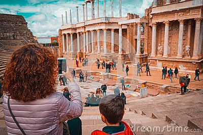 Tourist mother and child taking a picture in the antique Roman Theatre of Merida, Spain.