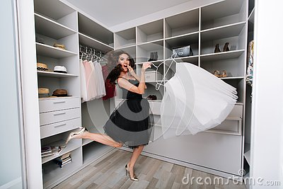 Enthusiastic young woman jumping in dressing room, nice wardrobe with skirt in hands. She`s happy with the choice. She`s