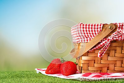 Picnic basket on a wooden table with a tablecloth and strawberries. relaxing on a picnic, and enjoyable in nature, with space