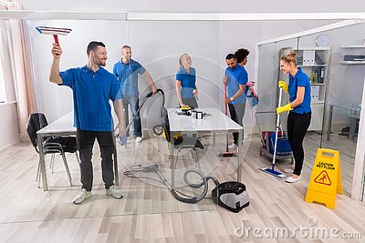 Group Of Skilled Janitors Cleaning Office