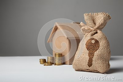 Brown bag with key logo. Gold coins and home paper house. The concept of renting and buying house