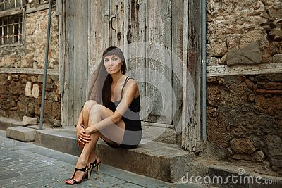 Outdoor lifestyle portrait of pretty young girl, wearing in black dress on urban background. Creative color toned image