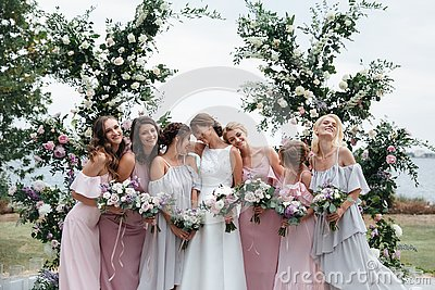 Beautiful elegant slim smiling bridesmaids in delicate pink beige summer dress on the wedding ceremony.