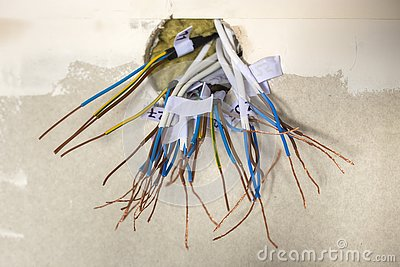 Electrical exposed connected wires protruding from socket on white wall. Electrical wiring installation. Finishing works in