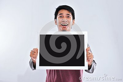 stock image of happy young handsome asian man holding and showing blank blackboard or board ready for your text