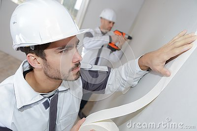 Painter worker protecting wall before painting at home improvement work