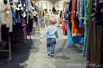 Cute caucasian blond toddler boy walking alone at clothes retail store between rack with hangers. Baby discovers adult shopping