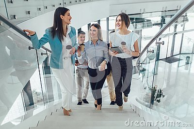 Businessmen and businesswomen walking and taking stairs in an office building