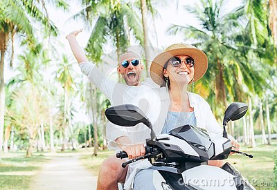 Laughing happy couple travelers riding motorbike during their tropical vacation under palm trees. Man emotionally raised hand up