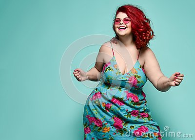 Lucky plus-size lady overweight woman in fashion sunglasses and colorful sundress happy dancing, celebrating