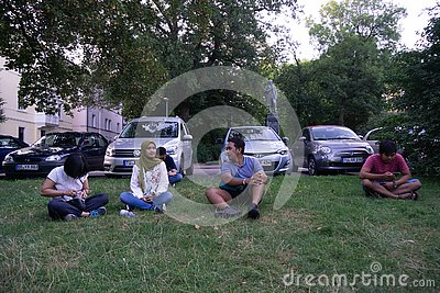 stock image of tubingen/germany-july 31 2018: a number of asian tourists were sitting on the lawn, near the car park, talking to each other