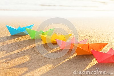 Colored paper boats row on sandy beach outdoors