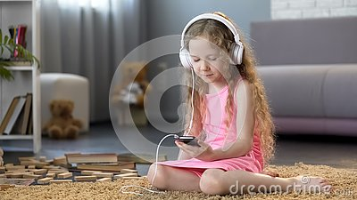 Girl in headphones using smartphone, learning pronunciation of foreign language